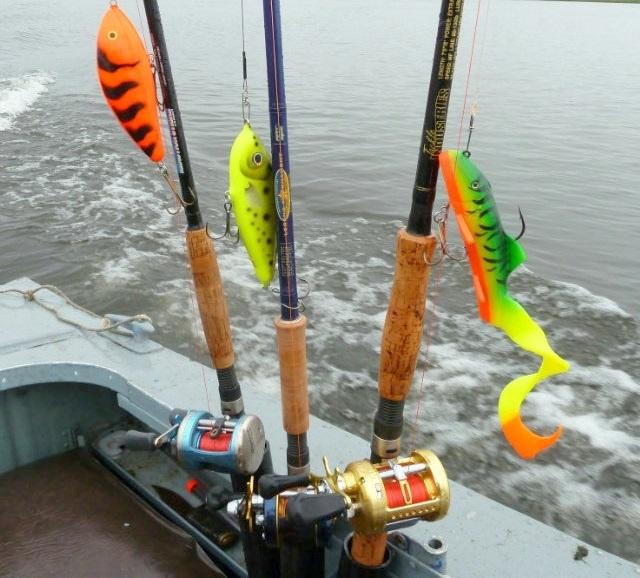 Джерковые спиннинг и приманки в лодке на фоне озера.