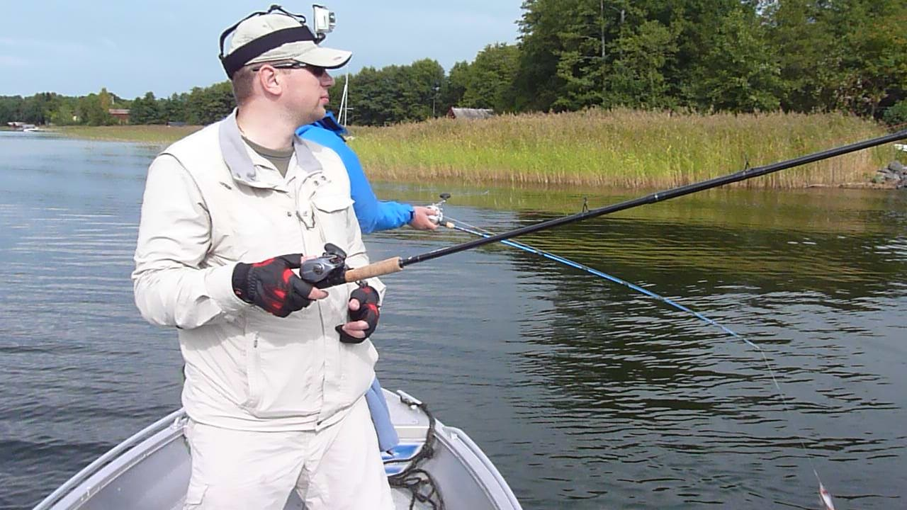 Рыболов в лодке рыбачащий на джерковую снасть